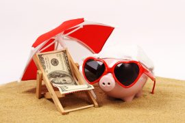 Summer piggy bank with heart sunglasses standing on sand
